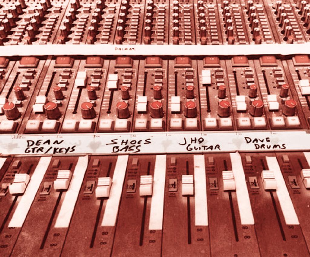 Exemple d'une table de mixage ( détail du bas ) avec ses tranches, potentiomètres et surtout, sa bande de rouleau adhésif sur laquelle sont inscrits les noms des musiciens auxquels se rattachent les pistes sonores et leurs paramètres respectifs.